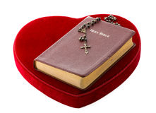 Bible and Rosary over a red velvet heart Royalty Free Stock Images