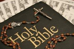 Bible sainte, rosaire et argent Photographie stock