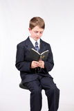 Bible School. Young boy seated reading a bible and holding a rosary Stock Photo