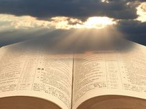 Bible spiritual light for mankind. Concept photo of open holy bible with sun rays shining through storm clouds depicting spiritual light for mankind stock photo