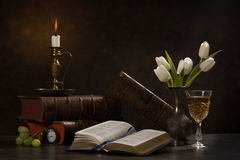 Bible Studies. Still life image of an open bible on a table along with a candle and candle holder, a vase of white tulips, a glass of wine, old books, a pocket royalty free stock photography