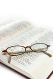 Bible Study. Open bible with folded reading glasses. Focus on glasses Royalty Free Stock Photography
