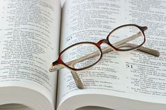 Bible Study. Open bible with folded reading glasses. Focus on glasses Royalty Free Stock Image