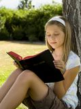 Bible Study. Cute young girl studying the Bible in a park Stock Photos