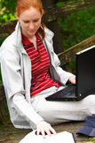 Bible Study. A young Christian woman doing Bible study outdoors with the help of a laptop computer. This image could also serve for other educational purposes royalty free stock photos
