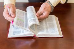 Bible study by a man of God or Pastor. Pastor or man of God reading and teaching the Bible to others and to himself in a small circle or house environment Stock Photography
