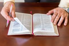 Bible study by a man of God or Pastor. Pastor or man of God reading and teaching the Bible to others and to himself in a small circle or house environment Royalty Free Stock Photo
