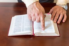 Bible study by a man of God or Pastor. Pastor or man of God reading and teaching the Bible to others and to himself in a small circle or house environment Royalty Free Stock Photos