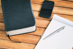 Bible Study Materials. A Bible, notebook and a smartphone over a wooden surface Royalty Free Stock Image