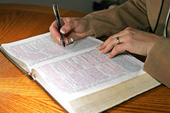 Bible Study Woman. A woman studies the Holy Bible nat a table (Christian Image, shallow focus point on Bible and hands stock photography