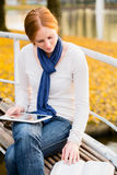 Bible Study. Woman studying the Bible with a tablet on her lap in a city park in the autumn Stock Image