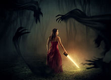 Bible and sword. A woman holds a sword out of a Bible with dark demons around stock photos