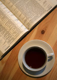 Bible on the table with the cup of coffee. Ready to read, opened english bible Stock Photos
