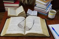 Bible. On the table lies a large open Bible, open the dictionary and stack of books. Notepad, pen and cup of coffee royalty free stock photo