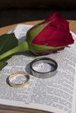Bible with two wedding rings and a rose. The book of Psalms is open and on the page is set a gold and a platinum wedding ring. A deep red rose lies next to the Stock Photo