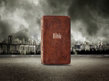 Bible on view of city in stormy sky. Background Stock Photography