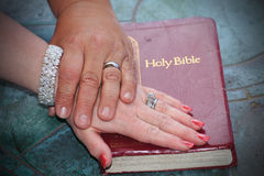 Bible Wedding Promise. His and her hands with wedding rings together on top of a bible. Shallow depth of field Stock Photography