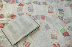 Bible on Wedding Ring Quilt Background. A Bible rests on a hand stitched wedding ring pattern quilt Stock Image