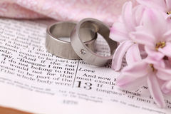 Bible and wedding rings. Titanium wedding rings on the Bible open to 1st Corinthians 13, a passage about love. Shallow dof Royalty Free Stock Photos