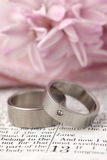 Bible and wedding rings. Titanium wedding rings on the Bible open to 1st Corinthians 13, a passage about love. Shallow dof Stock Photography