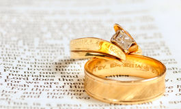 Bible & wedding rings. Two gold wedding rings rest on the marriage passage from Ephesians 5 in the Bible Stock Images