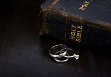 Bible with Wedding Rings. Weathered Bible and Wedding rings to convey a lasting marriage Royalty Free Stock Photography