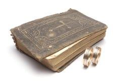 Bible & wedding rings. Closeup of closed Bible & wedding rings stock image