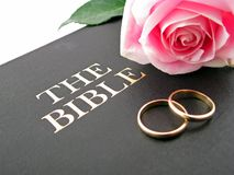 Bible, Wedding Rings and Rose. Two gold wedding bands on a leather Bible with a pink rose Stock Photography