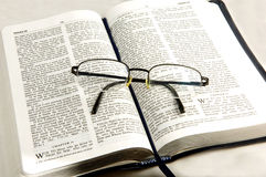 Bible whit eye glasses. A pair of reading glasses on top of a open bible, religious study's Royalty Free Stock Images