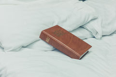 Bible on white sheets and bed Royalty Free Stock Image