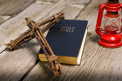 Bible and Wooden Cross. A wooden cross sits upon a bible next to a red antique lantern Stock Image