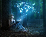 Bible and the world. A woman holds a Bible with glowing lights that show a map of the world royalty free stock photography