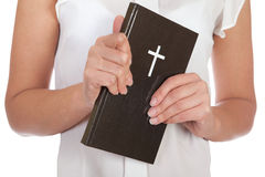 Bible. A young girl holding a bible in her hands royalty free stock image
