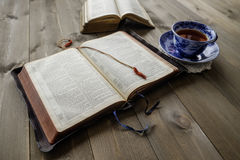 Bibles and cup of tea on wood table. Peaceful Christian religious scene of two open Bibles with cup of tea on wooden table background. Non trademark versions royalty free stock photo
