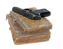 Bibles & gun. Two very old religious books and pistol on a white background Royalty Free Stock Images