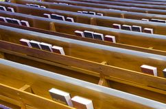 Bibles and Hymnals in Church Pews. Rows of pews in a church have book shelves holding Bibles and pews behind the seats stock images