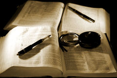 Bibles with Pens for Studying (sepia). A pair of Holy Bibles with pens and a magnifying glass, representing studying the bible in depth (sepia tint, shallow stock images