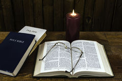 Bibles. Three bibles on wood desk one open with glasses and candle Stock Photo
