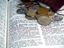 Biblia abierta en el libro de proverbios con las monedas Foto de archivo