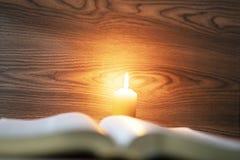 Biblia bajo luz de una vela y concepto santo cristiano de la inspiración fotos de archivo