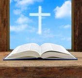 Biblia chrześcijanina krzyża światła nieba otwarty widok Fotografia Royalty Free