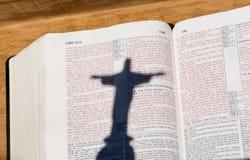 Biblia con las cartas y la sombra rojas del Jesucristo Imagenes de archivo