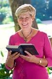 Biblia de la lectura de la mujer Imágenes de archivo libres de regalías