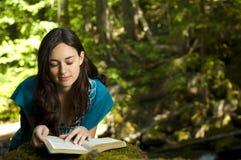 Biblia de la lectura de la mujer joven Foto de archivo