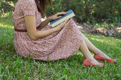Biblia de la lectura de la mujer joven en parque natural Foto de archivo