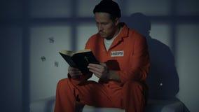Biblia de lectura masculina religiosa encarcelada, condenando en los pecados, sintiendo culpables almacen de video