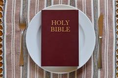 Biblia en una placa de cena con los cubiertos Fotografía de archivo libre de regalías