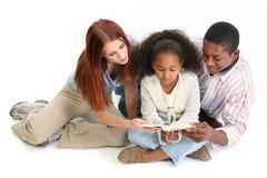 Biblia interracial junto Ov de la lectura de la familia Imagen de archivo