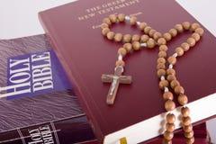 Biblia santa con el rosario en la pila de libros viejos foto de archivo libre de regalías