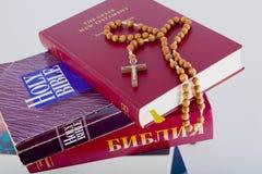 Biblia santa con el rosario en la pila de libros viejos imágenes de archivo libres de regalías